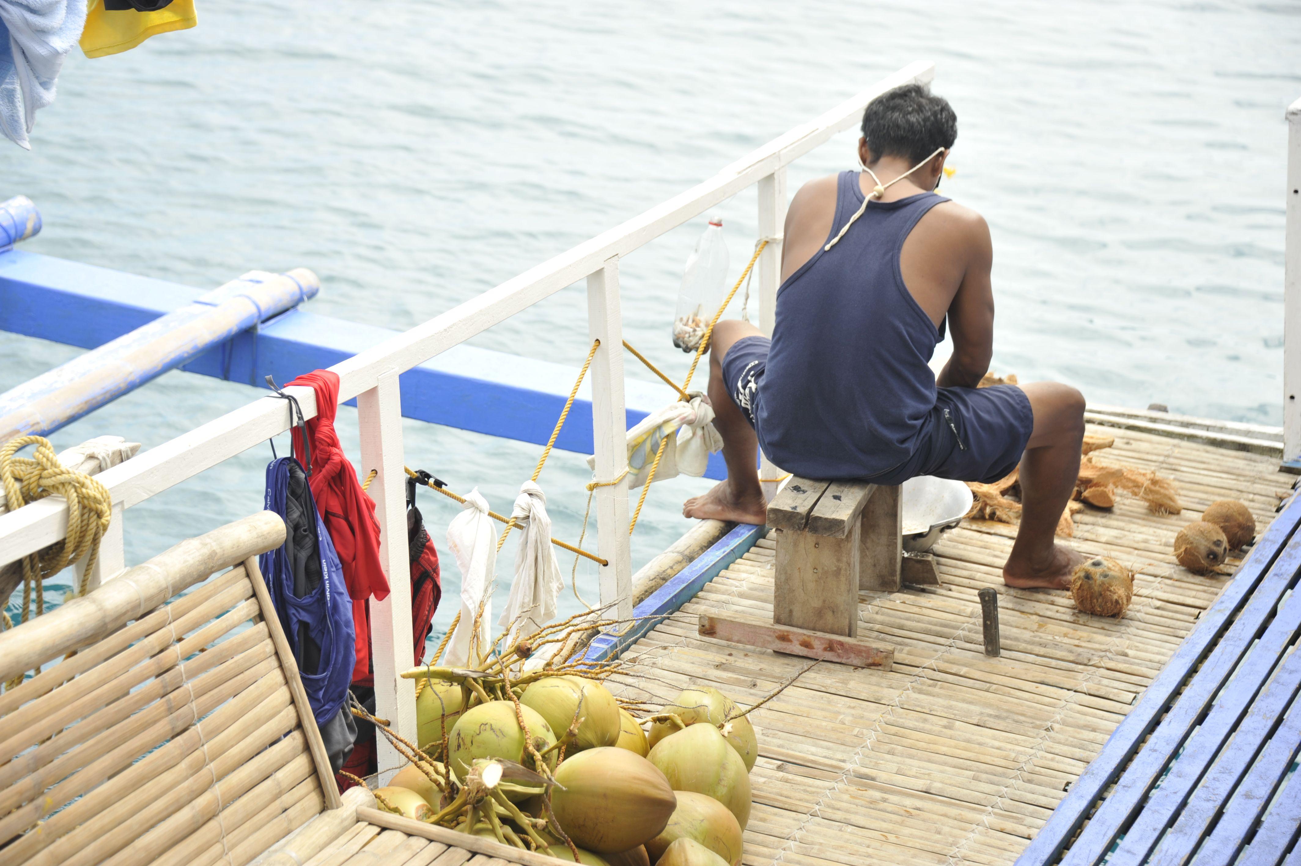 Un membre de l'équipage Tao en train de râper des noix de coco pour en faire du lait