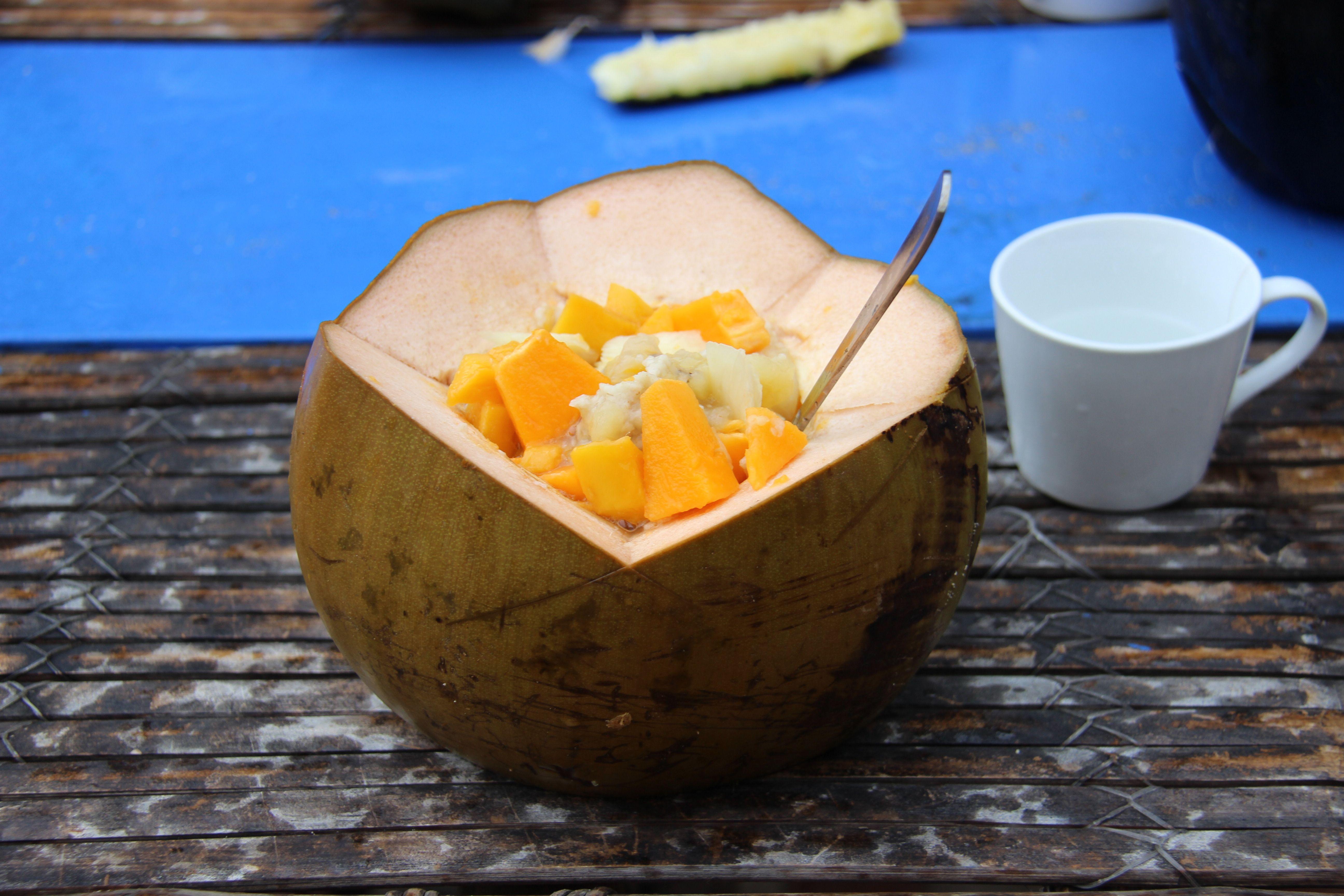 Porridge du matin et fruits exotiques frais servis dans une noix de coco